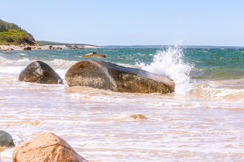 喷洒在马萨葡萄园岛,麻省的大岩石的海浪 免版税图库摄影