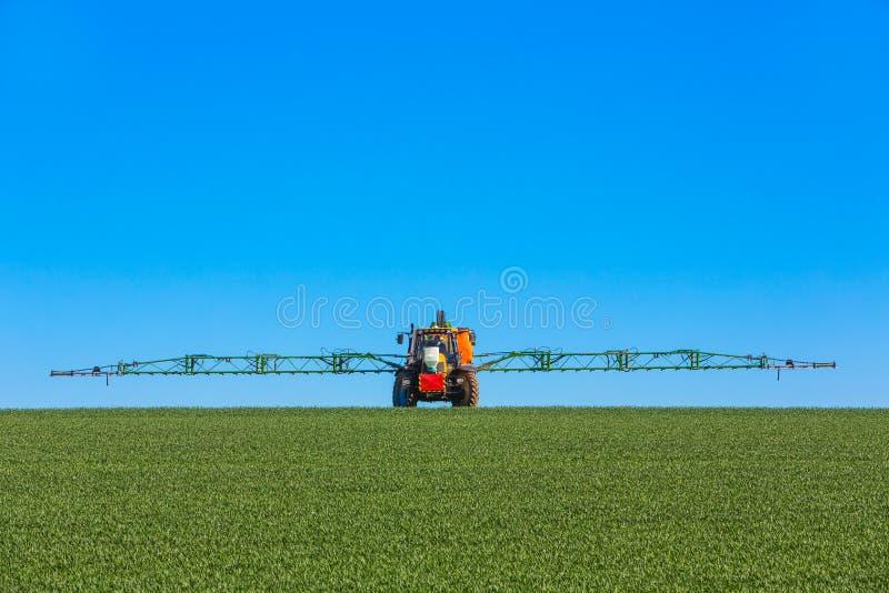 喷洒领域的拖拉机 免版税库存照片