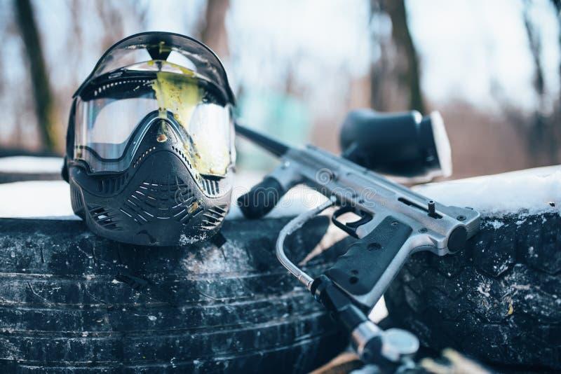 喷溅的迷彩漆弹运动面具和标志枪 免版税库存照片