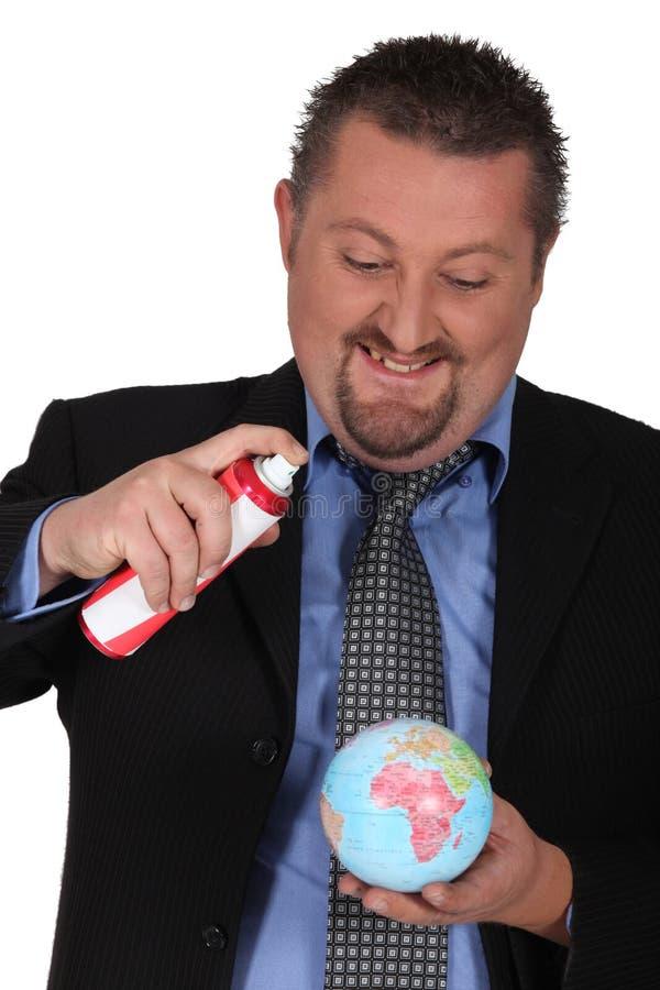 喷洒地球的生意人 免版税库存照片