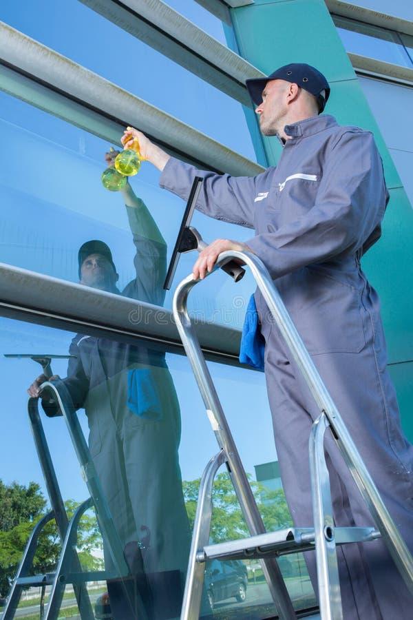 喷洒的和清洗的玻璃窗 免版税库存图片