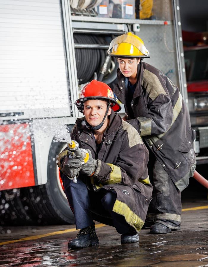喷洒水的确信的消防队员在实践期间 库存照片