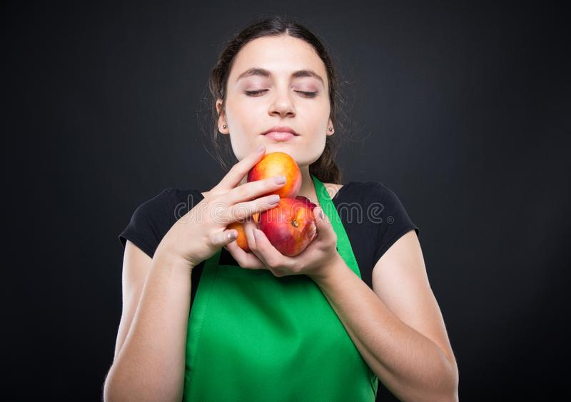 嗅到一些新鲜和甜油桃的少妇 免版税库存照片