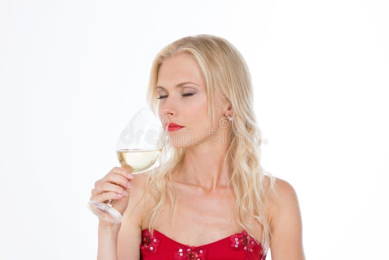 嗅到一杯白葡萄酒的北欧女孩 库存图片