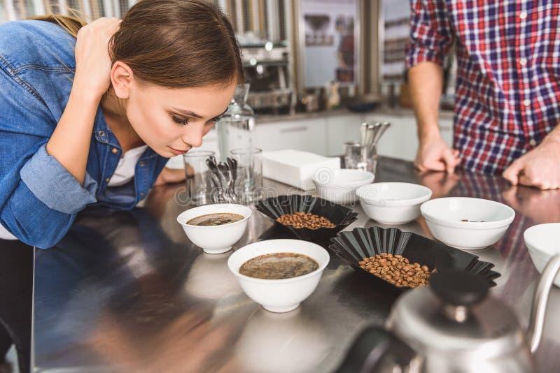 嗅到做的咖啡的被集中的女孩 免版税库存照片
