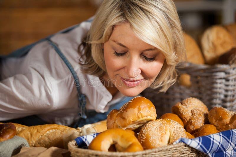 嗅到各种各样的甜食物的女职工 库存照片