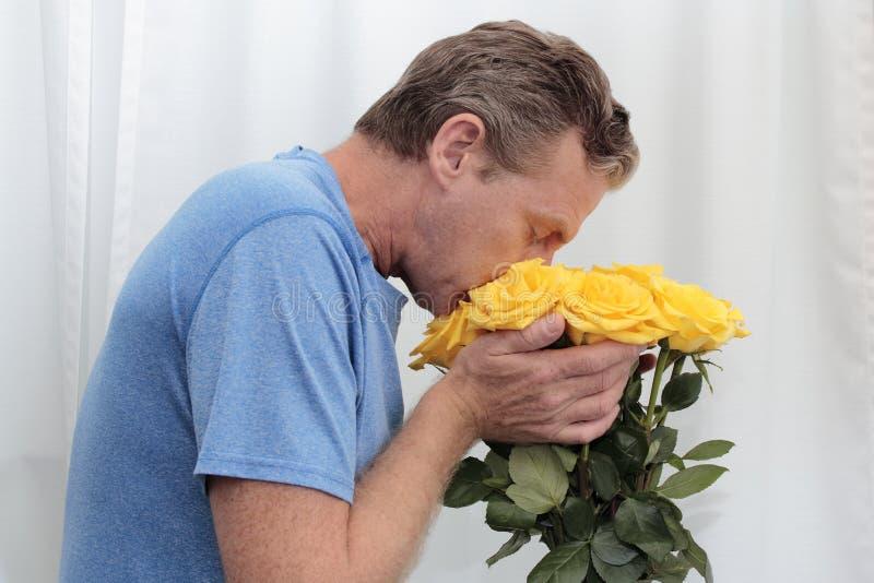嗅到和拿着玫瑰的黄色花束男性 免版税库存照片