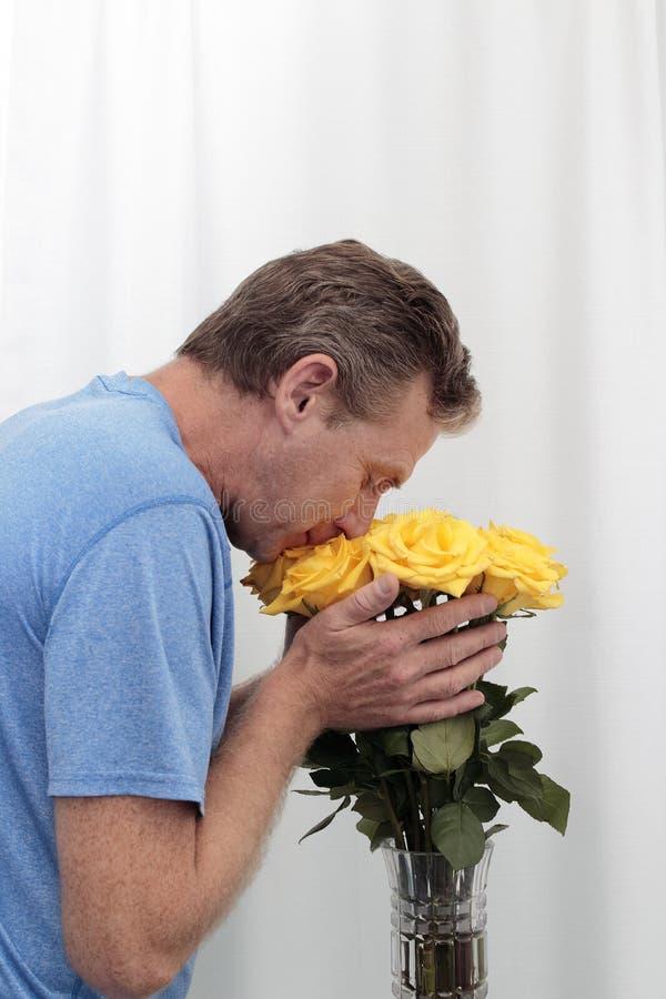 嗅到和拿着黄色玫瑰花束的人 免版税库存照片
