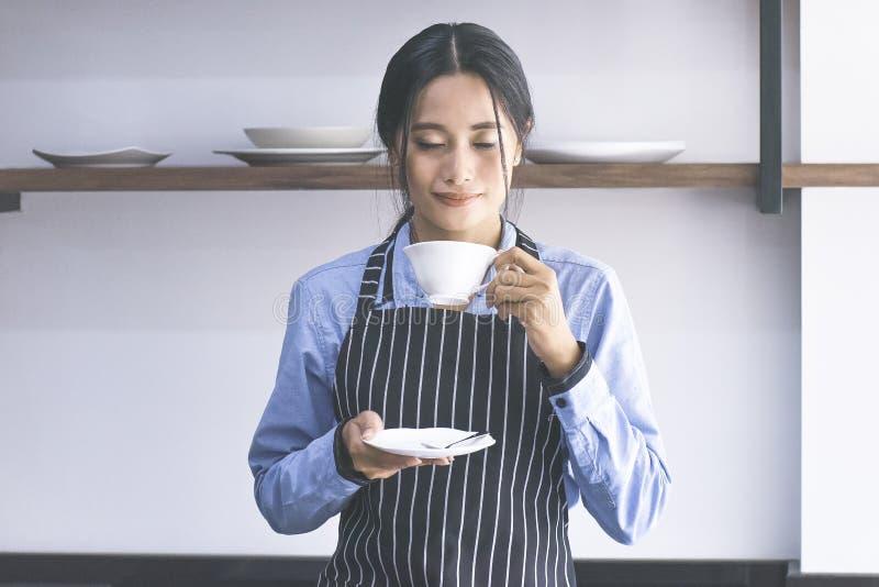 嗅到咖啡的亚裔barista妇女 库存图片