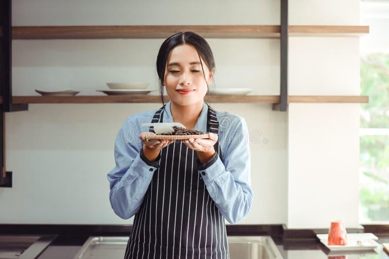 嗅到咖啡的亚裔barista妇女 图库摄影