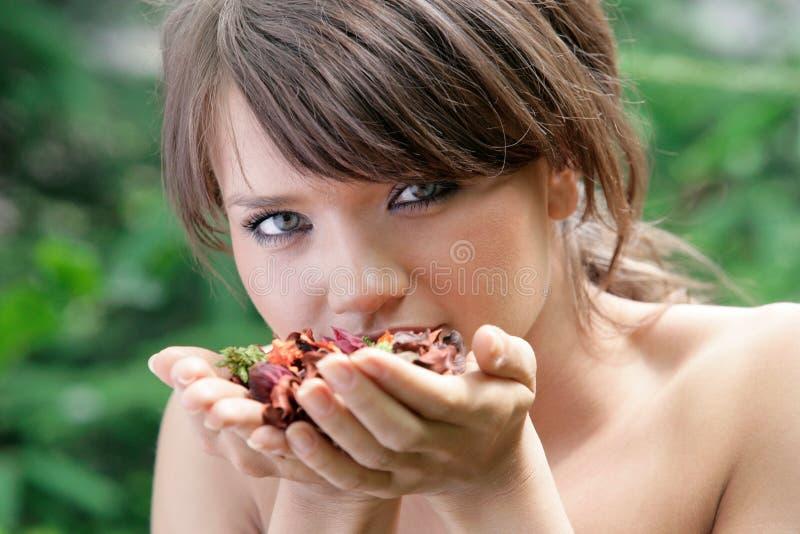 嗅到干花的年轻深色的妇女 图库摄影