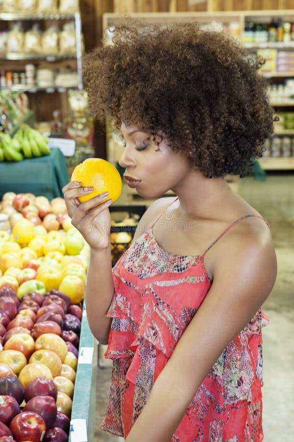 嗅到新鲜的桔子的非裔美国人的妇女侧视图在超级市场 库存照片