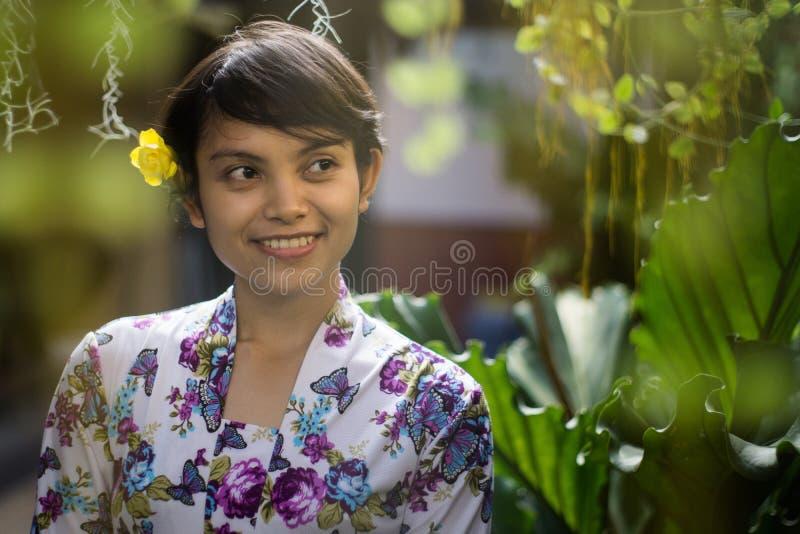 嗅到有自然绿色背景的美丽的短发亚裔印度尼西亚女孩 使用花卉样式传统衬衣和a的她 免版税库存照片