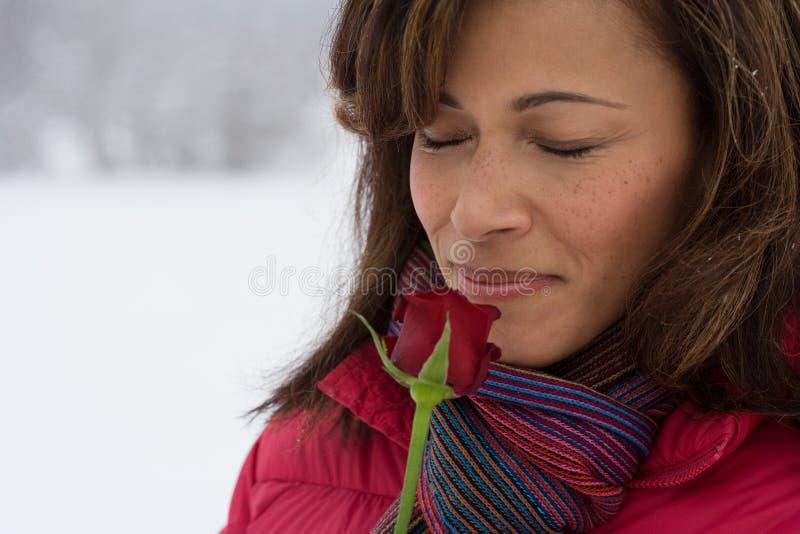 嗅到玫瑰的成熟妇女 免版税库存图片