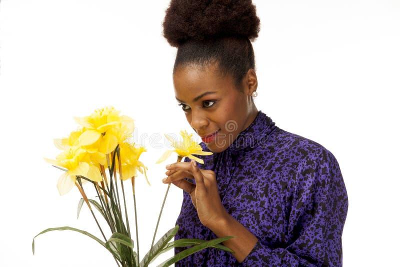 嗅到鲜花的非裔美国人的妇女 库存图片