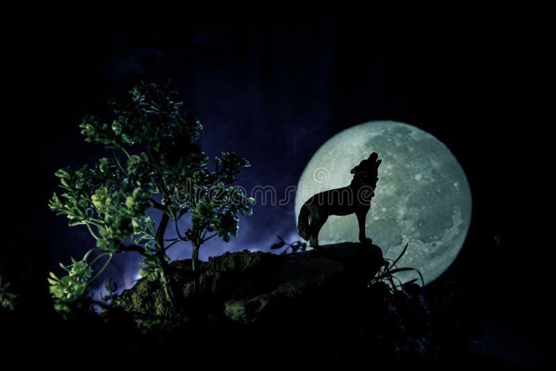 嗥叫狼剪影反对黑暗的被定调子的有雾的在剪影嗥叫对满月的背景的和满月或者狼 你好 免版税图库摄影