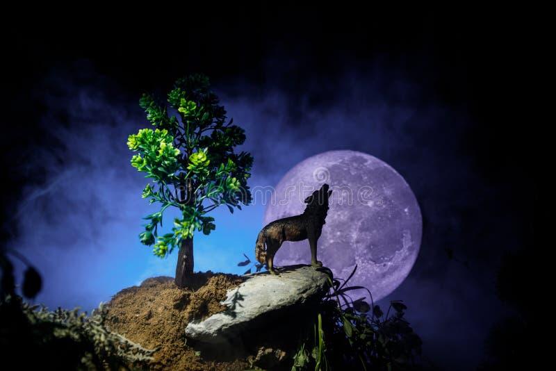 嗥叫狼剪影反对黑暗的被定调子的有雾的在剪影嗥叫对满月的背景的和满月或者狼 你好 免版税库存图片