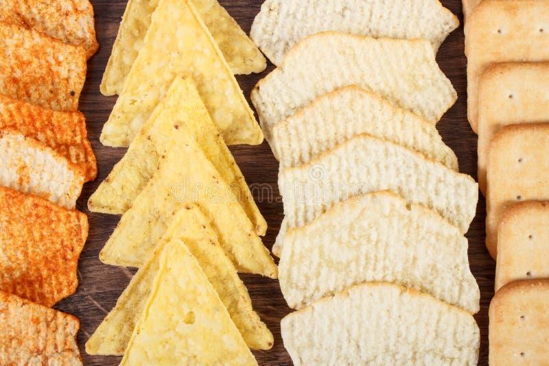 嘎吱咬嚼的曲奇饼和盐味的油炸马铃薯片,不健康的食物的概念 免版税库存图片