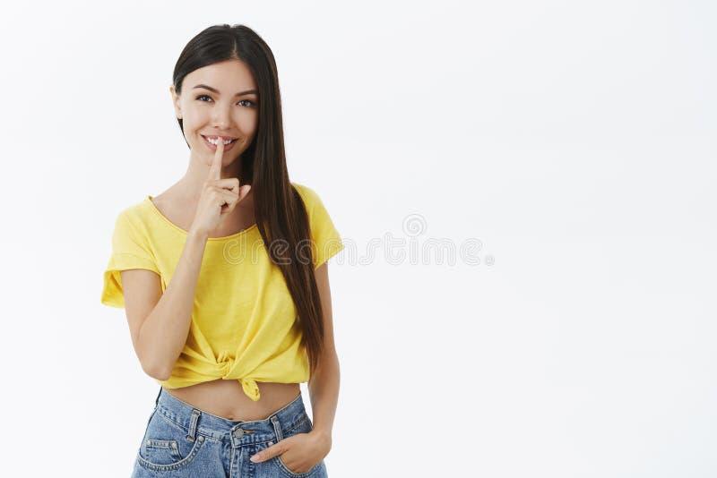 嘘保留它在我们之间 迷住时髦黄色T恤杉做的神奇和私秘年轻女人嘘姿态与 库存图片