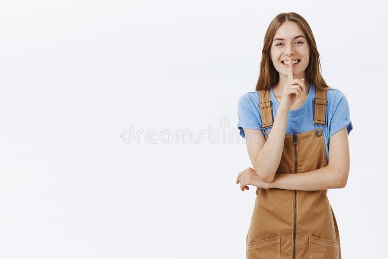 嘘女孩想要份额秘密 迷人的友好俏丽的妇女画象棕色粗蓝布工装和蓝色T恤杉的 图库摄影