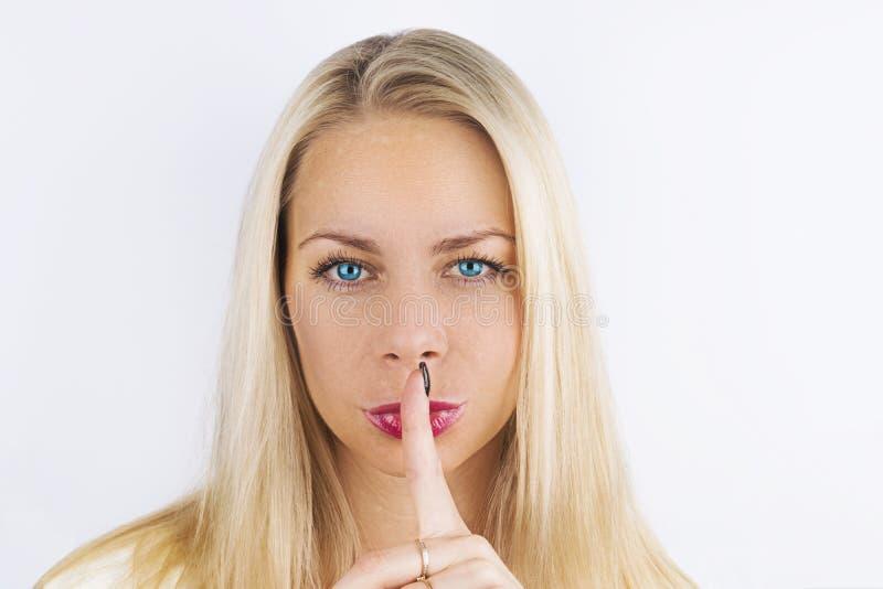 嘘!妇女` s秘密 有握她的手指的蓝眼睛的美丽的白肤金发的妇女对她的在一个姿态的桃红色嘴唇沈默的 做si 库存图片