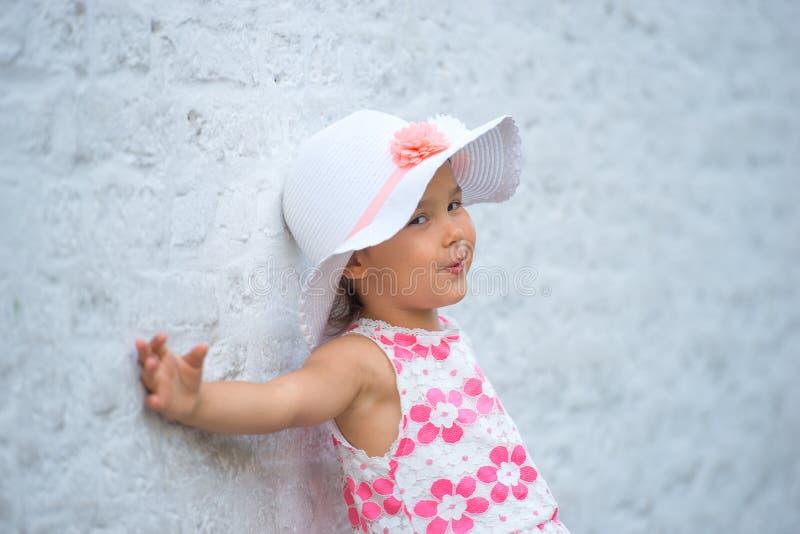 嘲笑一个空白的空的砖墙的愉快的小女孩 图库摄影