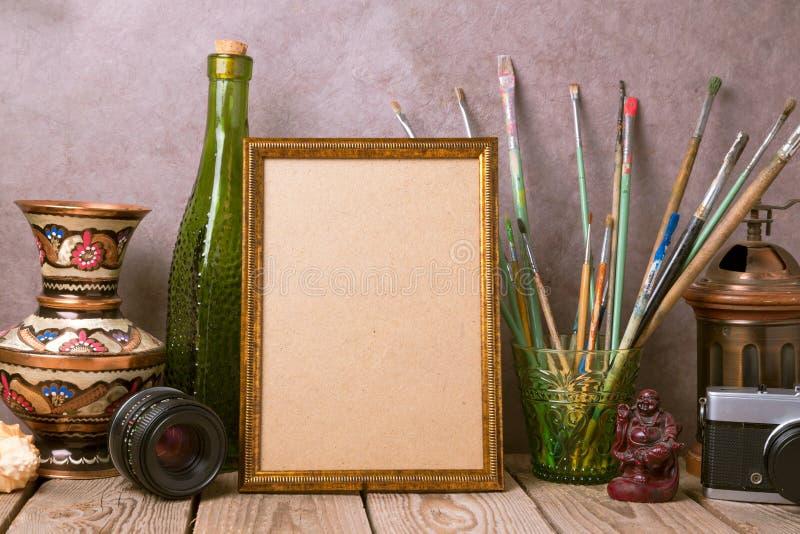 嘲笑与葡萄酒艺术性的对象的海报框架和在木桌上的老照相机 免版税库存图片