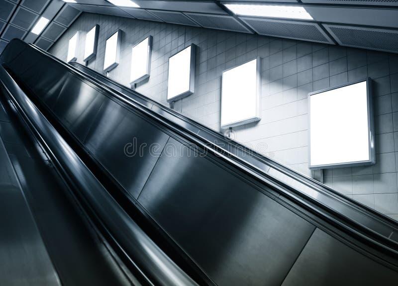 嘲笑在地铁站的垂直的海报与自动扶梯 库存照片
