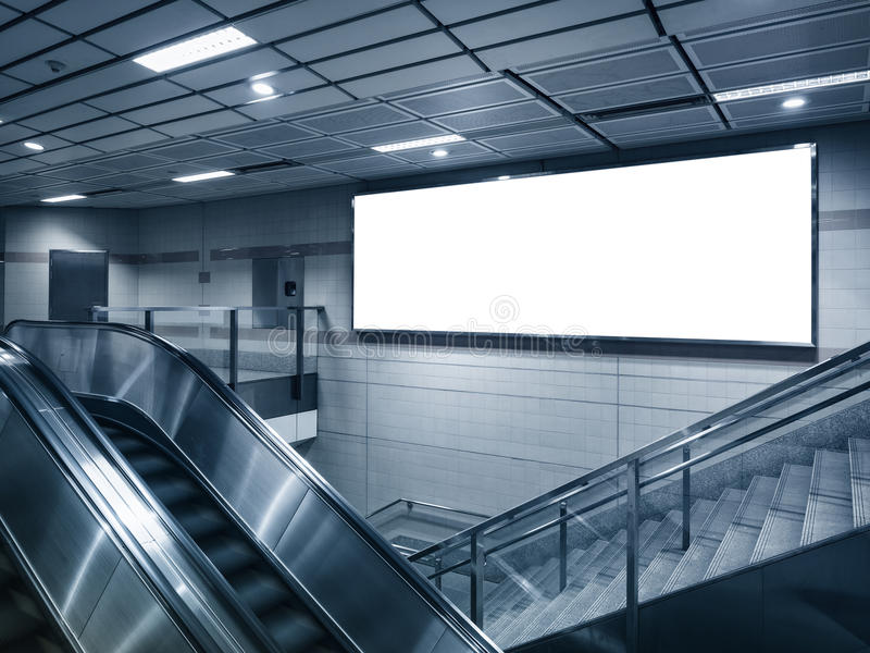 嘲笑在地铁站的广告牌与自动扶梯 库存照片