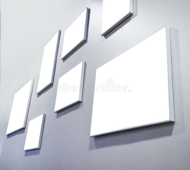嘲笑在灰色墙壁画廊显示的空白的海报 库存照片