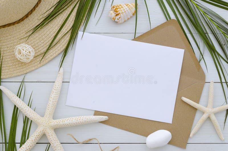 嘲笑在白色木背景的卡片模板 热带棕榈叶、夏天帽子、seastars和工艺信封 免版税库存图片
