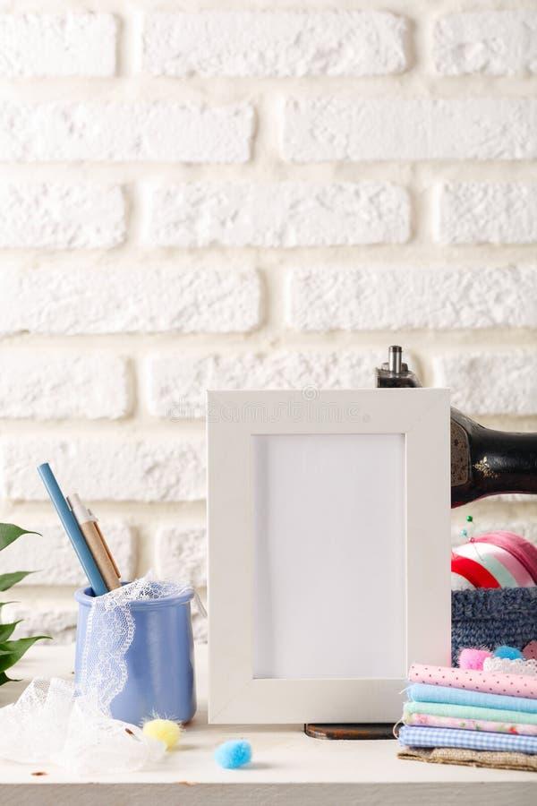 嘲笑在白色的白色框架砖墙背景、葡萄酒缝纫机和堆纺织品 顶楼内部 图库摄影