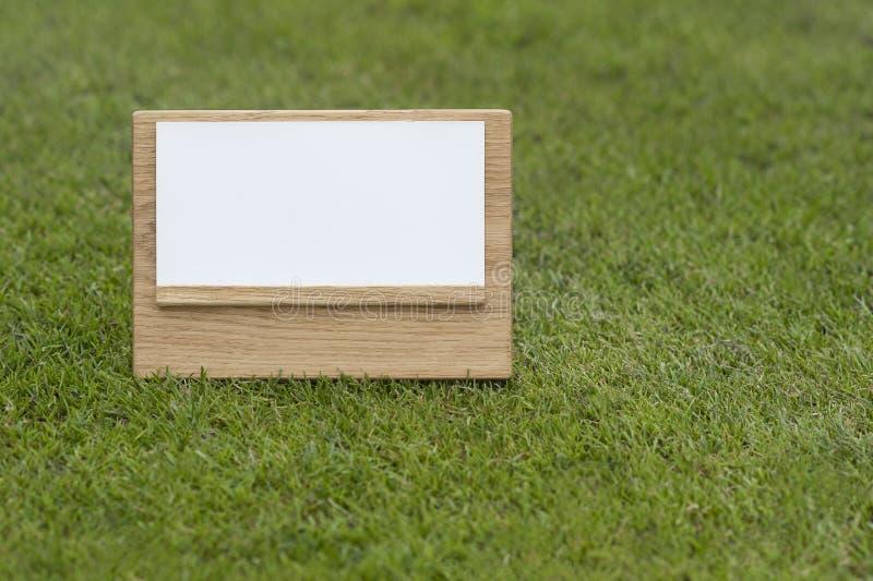 嘲笑在绿色背景的木标志 免版税库存图片