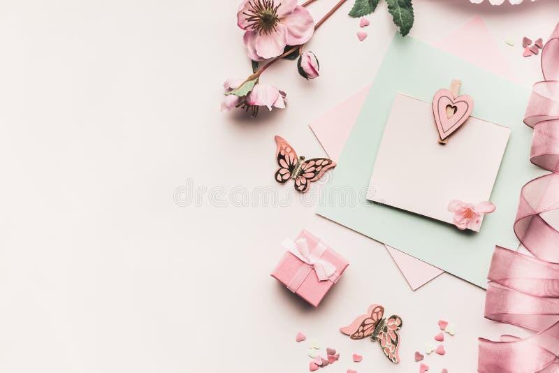 嘲笑在苍白淡色的女性假日贺卡与花、礼物盒、丝带和心脏在白色桌面backgrou 免版税图库摄影
