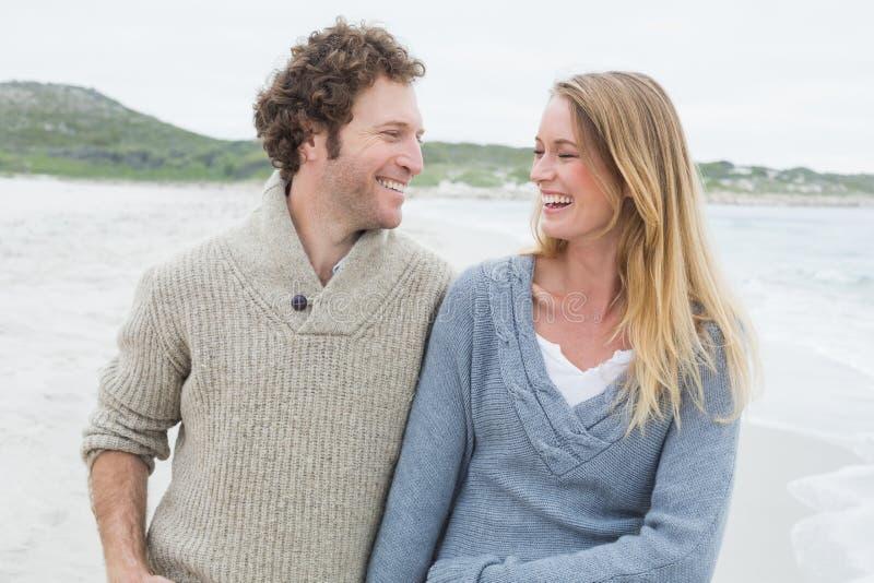 嘲笑海滩的愉快的偶然夫妇 免版税图库摄影