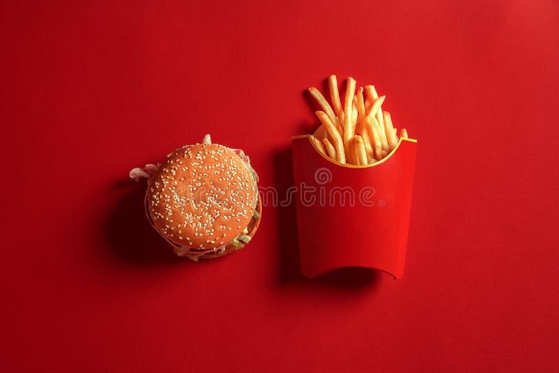 嘲笑的概念汉堡和炸薯条的在红色背景 复制文本和商标的空间 免版税库存照片
