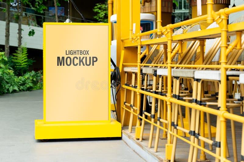 嘲笑黄灯箱子在您的广告的一个城市 空白嘲笑您的文本的垂直的街道海报广告牌 免版税库存照片