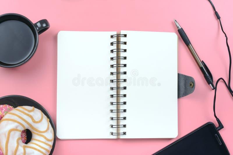 嘲笑 与白页的笔记薄在春天在构成的中心 附近一杯咖啡、油炸圈饼和a 免版税库存照片