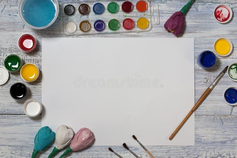 嘲笑 创造性的空间 在葡萄酒木桌上的艺术家工作区:水彩,白皮书,树胶水彩画颜料油漆,画笔,浇灌  免版税图库摄影