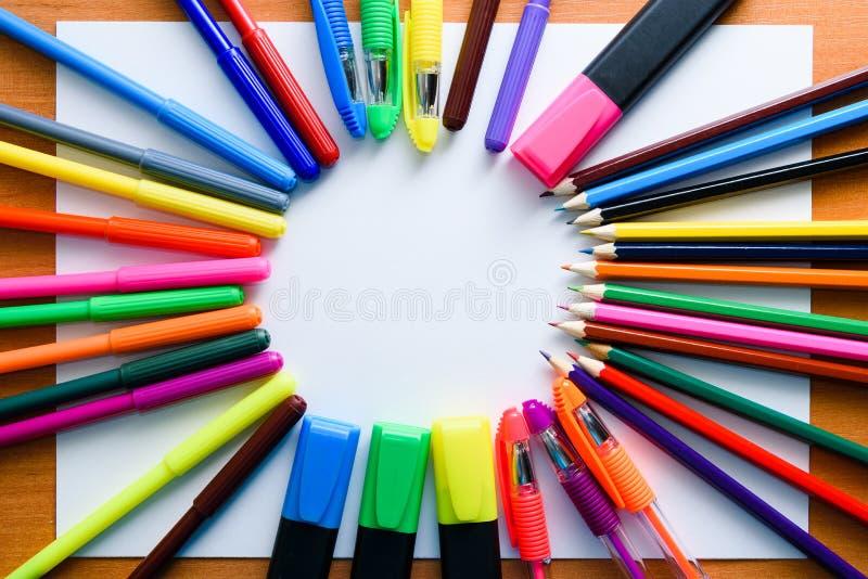 嘲笑 创造性的空间 在轻的木桌上的艺术性的工作工具:色的铅笔,笔,标志 免版税库存照片