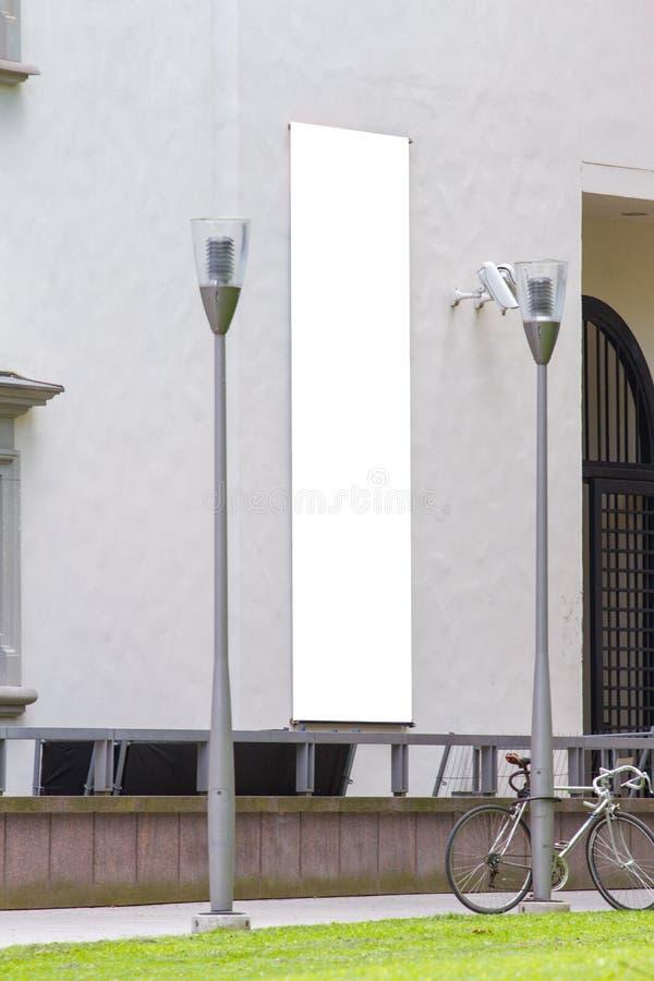 嘲笑 在大厦门面的空白的白色垂直的横幅 空的广告旗子嘲笑在墙壁上 图库摄影