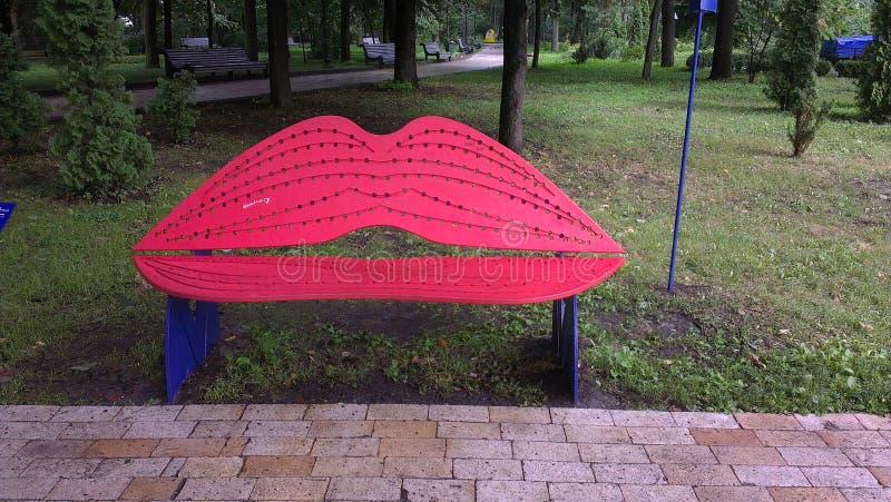 嘴唇型亲吻的长凳在城市公园 红色的嘴唇 免版税库存图片