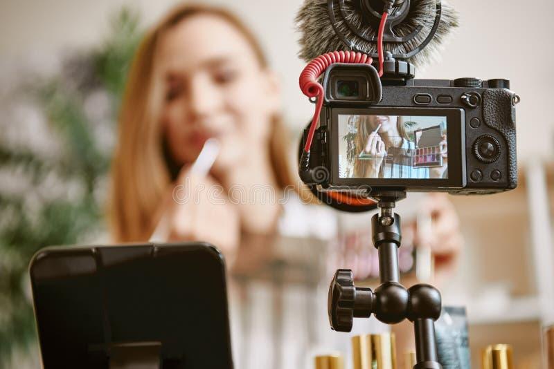 嘴唇 数码相机接近的照片有尝试一种新的唇膏颜色的年轻博客作者的,当在网上播放时 库存图片