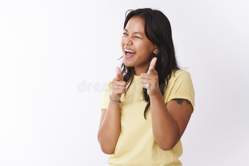 嘿什么  友好和外出的无忧无虑的嬉戏的玻利尼西亚人做手指手枪的黄色T恤杉的被刺字的女孩和 免版税库存照片