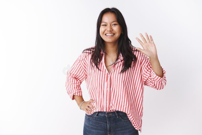 嘿好朋友什么  友好和善社交的逗人喜爱的迷人的亚洲人女性在镶边女衬衫招呼摇手的新手快乐 免版税库存图片