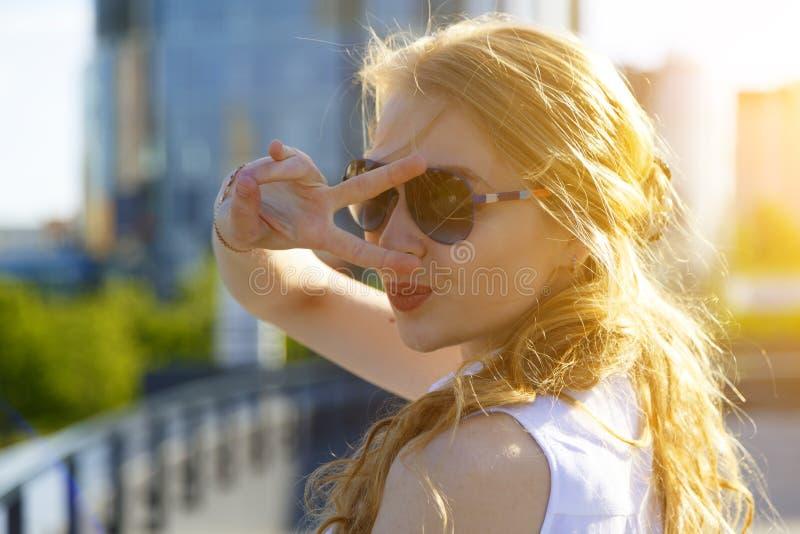 嘿微笑您 厚颜无耻和逗人喜爱的玻璃明亮头发的闪光魅力白肤金发的妇女画象愉快地显示和平胜利 免版税库存照片