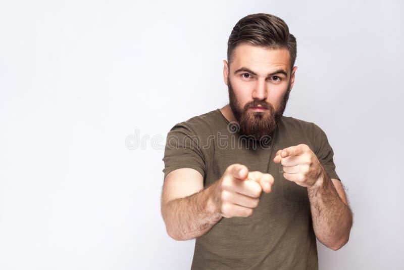 嘿您!严肃的有胡子的人画象有深绿T恤杉的反对浅灰色的背景 库存照片
