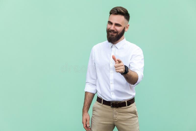 嘿您!年轻成人有胡子的人,指向手指和看照相机 在浅绿色的背景 室内 库存照片