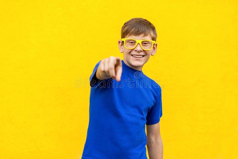 嘿您! 黄色玻璃的幸福有雀斑的男孩,指向finge 库存照片