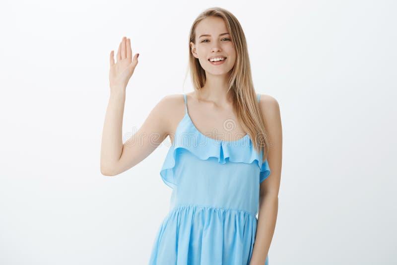 嘿见到你很高兴 蓝色礼服的友好的悦目迷人的典雅的女孩有公平的毛骨悚然棕榈和挥动的 库存图片
